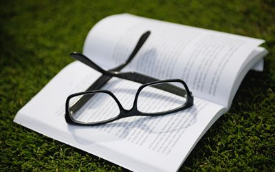 glasses on a book, green grass, mood, white paper, reading book concepts
