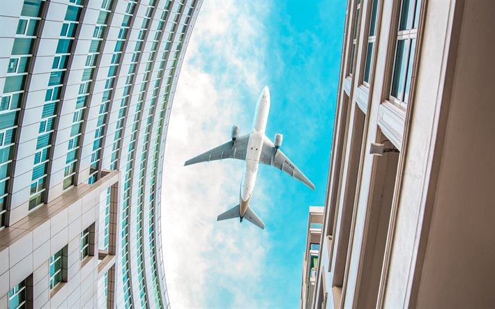 passenger plane over buildings, plane over the city, airplane bottom view, blue sky, building, air travel concept