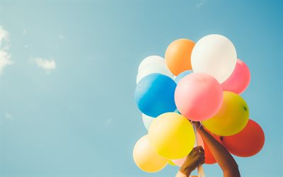 colorful balloons in the hand, bundle of balloons, blue sky, mood concepts