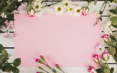 Roses, chrysanthemums, pink paper, pink flowers, wooden background, template for congratulations
